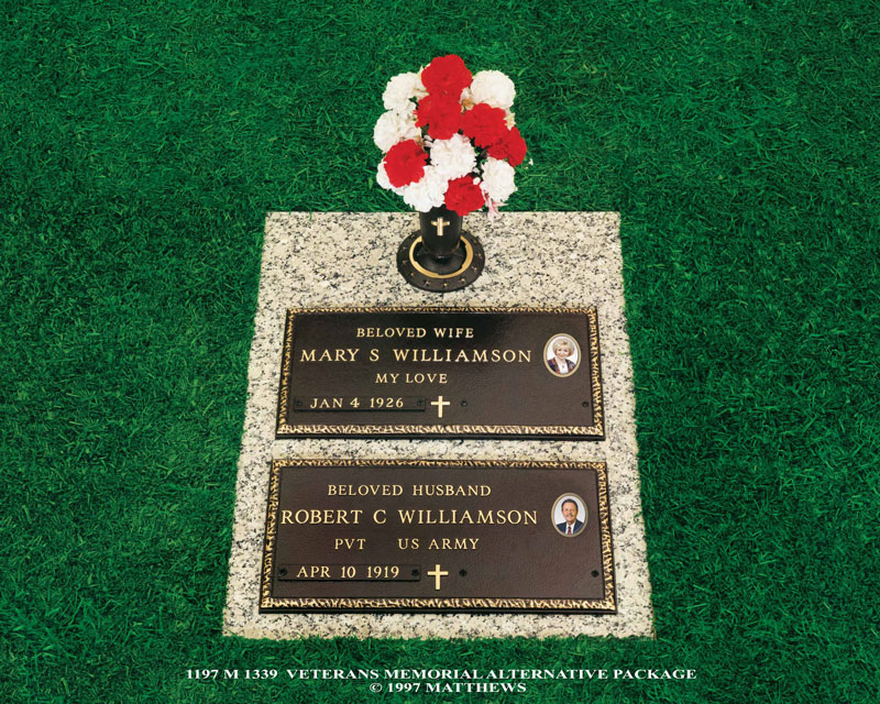 stone grave marker with two bronze plaques and red and white flowers